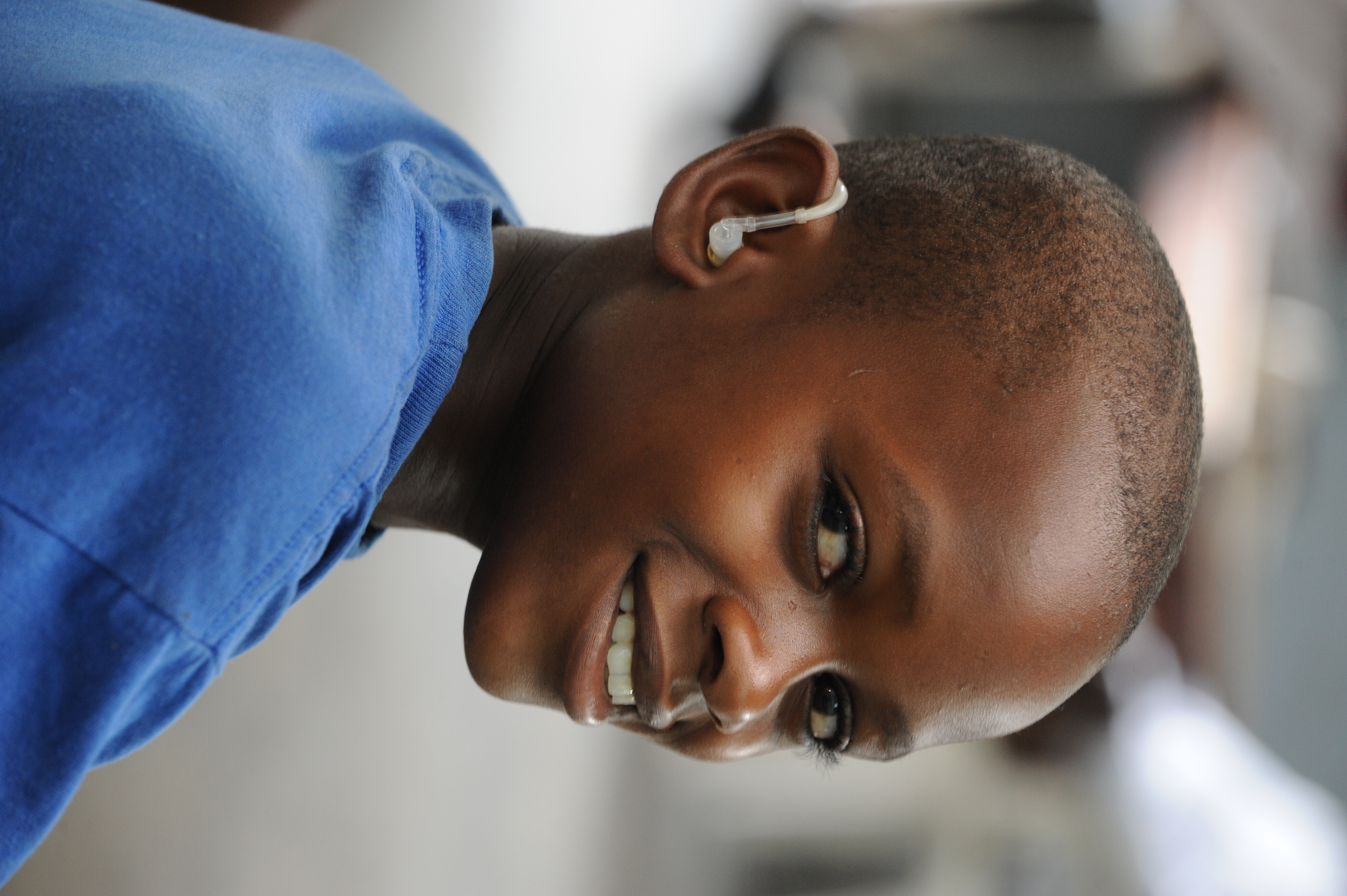Black boy using a hearing aid. Cover Image